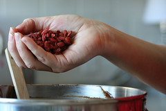 goji berries going into chocolate cupcake batter