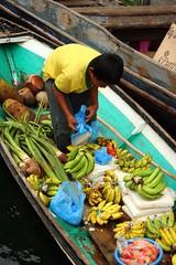 halin (Farl) Tags: wood travel boy water colors fruits bag island boat commerce market muslim philippines tomatoes culture banana plastic vendor tradition floatingmarket tawitawi cassava samal sitangkai panggi armm