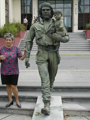 Che Statue outside local communist party HQ in Santa Clara. Woman is explaining the symbolism of the different items found on the statue.<br /> There is a slot on the statue's back. Its real purpose is to prevent the statue from cracking as the material expands and shrinks, but it makes the statue look like a bank. As our professor joked, it was a fitting symbol of the regime's selling out, or at least capitalizing, on Che's revolutionary chicness.