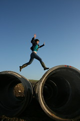 Climb on giant tubes instead (squacco) Tags: blue sky danger zoe concrete flying jump jumping tube tubes hop skip wellies leap leaping prance deeplyvale millsinhills open2007
