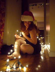 Merry Christmas 8 (QXZ) Tags: christmas light party portrait woman holiday cute girl beautiful beauty brooklyn pose glamour pretty december tara feminine seasonal posed 2006 hallway christmaslights sparkle actress santahat tangle blackdress woodflooring extrovert