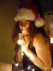 Merry Christmas 2 (QXZ) Tags: christmas light party portrait woman holiday cute girl beautiful beauty brooklyn pose glamour pretty december tara feminine seasonal posed 2006 hallway christmaslights sparkle actress santahat tangle blackdress woodflooring extrovert