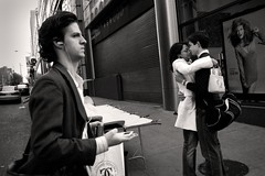 Street Embrace (shveckle) Tags: nyc newyorkcity people bw man poster hug couple ipod manhattan streetphotography embrace wechsler shveckle sideeye