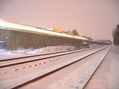 A departing Green Line train and the parallel Camden Line on a snowy night.
