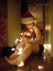 Merry Christmas 7 (QXZ) Tags: christmas light party portrait woman holiday cute girl beautiful beauty brooklyn pose glamour pretty december tara feminine seasonal posed 2006 hallway christmaslights sparkle actress santahat tangle blackdress woodflooring extrovert