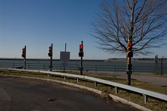 The Four Stops (and that show off one on the right) (Gregory Pleau) Tags: road red usa newyork tree water sign buffalo lakeerie signals redlight stoplights showoff niagarariver gregorypleau