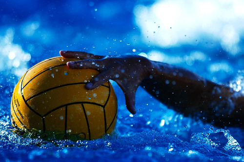 A UCSD women's water polo player reaches for the ball.