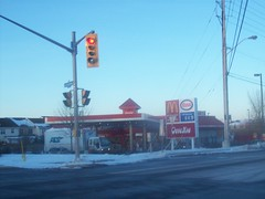 Super Bizarro Hybrid Esso Station. (Steve Brandon) Tags: winter snow ontario canada trafficlights truck restaurant parkinglot hiver ottawa fastfood suburbia location cargo mcdonalds gasstation cheeseburger hamburger drivethru delivery suburb neige bigmac hybrid esso  drivethrough conveniencestore goldenarches selfservice servicestation mcdo ats petrolstation gaspumps franchise  fillingstation quickie newsagents stationservice mcdrive eggmcmuffin dpanneur  libreservice essostation sausagemcmuffin feuxdecirculation huntclubroad   huntclubrd ruehuntclub ottawaroad32 lorrygreenbergdrive lorrygreenbergdr promenadelorrygreenberg andlauertransportationservices