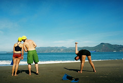 stretching on china beach (lomokev) Tags: california sea people beach water sport fuji superia stretch chinabeach swimmers triathlon foundinsf fujisuperia fujisuperia400 jenniferellison  deletetag nikonos