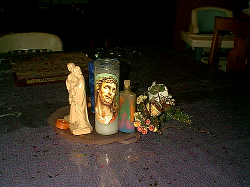 A candle of the crucified Christ next to a bottle of colored sand