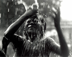 water fall (richard thomson) Tags: boy blackandwhite bw topf25 water asia cambodia 35mmfilm drama fp4 nikonfe2 pouringwater dramaticportrait lpmotion