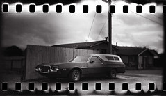 ranchero. (shoegazer) Tags: light sky house car clouds fence shadows ranchero manilla holga35mm kodaktmax100 sprocketholes