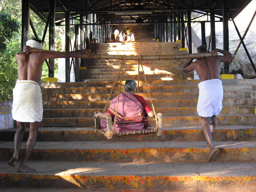 An old lady being carried up the stairs to the temple..
