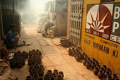 D H A R A V I (Dharmesh Thakker) Tags: india man yellow canon 350d paint smoke ad pots mumbai sion slum birla photophilosophy dharavi