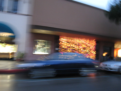 Driving past the empty furniture store with art installations in the windows