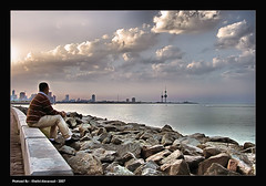 City meditation (khalid almasoud) Tags: city light sun 3 man clouds canon eos seaside rocks towers 9 24 meditation kuwait 105 khalid 2007 xti 400d almasoud
