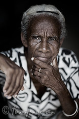 An elderly Cuban woman looks on pensively. (tommyimages_com) Tags: old portrait latinamerica vertical closeup female serious cuba trinidad pensive desaturated cuban wrinkles dignity sanctispiritus blackperson whitehair elderlywoman afrocuban spanishspeakingcountries sanctispritus sanctispritus