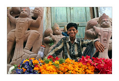 Hanuman with flowers (Elishams) Tags: city flowers india smile photo colours child indian holy varanasi hanuman worker mali indianarchive kashi mala streetseller streetvendor banaras benares murti northindia uttarpradesh mtier