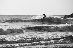 Morning Style (haddartist) Tags: ocean oceanside oceanfront coast coastal surf surfer surfing surfboard style stylish throwingspray turn turning silhouette silhouetted wave waves lines lineup lip spray foam ripples rippled glassy reflection rocks jetty sky clear clarity morning light sunny sunshine backlight highlights monotone bw blackandwhite blur bokeh virginiabeach virginia