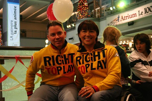 Chantal Petitclerc and Warren Spires, two people wearing 'right to play' shirts and sitting next to what appears to be an ice skating rink. One of the people, Chantal, is in a wheelchair.
