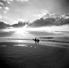 a moment (czuczy) Tags: sunset sun beach hawaii three holga waves surfer 2006 northshore rays bodyboarder