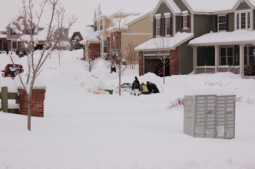 Neighbors try to get a car unstuck from a deep drift