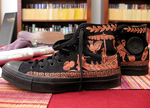 Black Chuck Taylor sneakers, with Greek-style vase           painting on them.