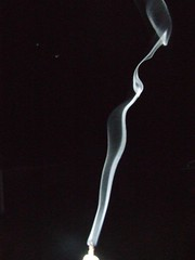 smoke from a candle against a black night sky