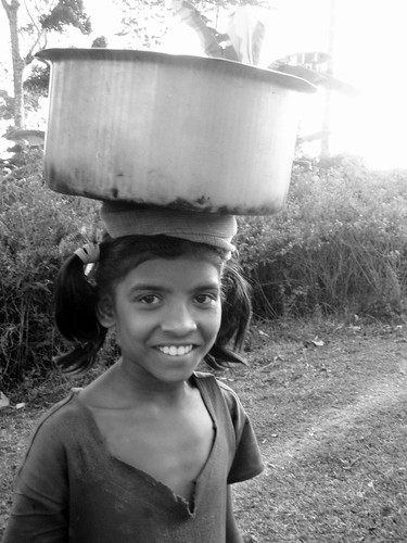 Young indian girl bringing water to her home