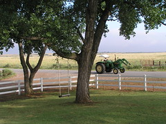 White rail fence, tree swing and a tractor
