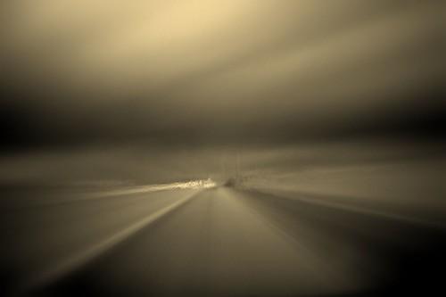 Fotografía abstracta tomada desde un vehículo en movimiento, el fondo de una carretera en tonos grises parece un tunel hacia el infinito
