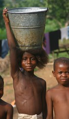 water bearer (LindsayStark) Tags: africa travel portrait people girl children war sierraleone conflict humanrights humanitarian displaced idpcamp refugeecamp idps idp humanitarianaid emergencyrelief idpcamps waraffected carryingloads