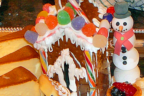 A snowman beside his gingerbread house.