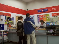 A couple sending a package at a Canada Post postal counter. (Steve Brandon) Tags: people ontario canada boyfriend scale postes geotagged girlfriend couple counter cue post mail candid interior ottawa postoffice line queue suburb nepean cashregister envelopes packages unaware lineup canadapost shoppersdrugmart  pamphlets unsuspecting postalworker pharmaprix  postescanada expresspost bureaudeposte merivaleroad merivalemall merivalerd ruemerivale xpresspost cheminmerivale centredachatsmerivale postalclerk postalcounter