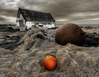 Orange plastic  buoy, rusted iron buoy and boat house ...