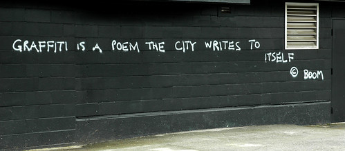 "white graffiti on a black painted wall: ""graffiti is a poem the city writes to itself"""