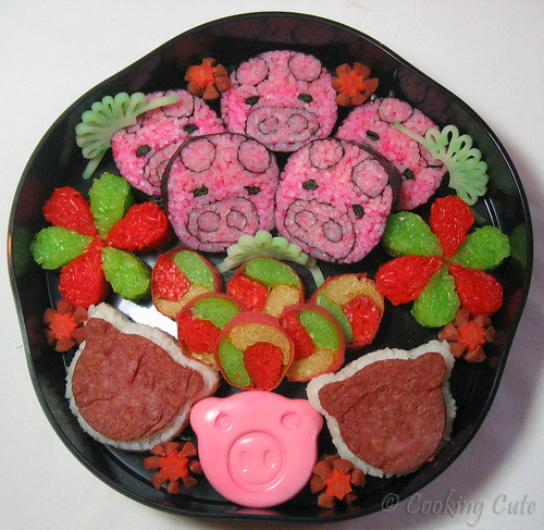 [jyubako with pig-shaped sushi, pig-shaped egg and spam nigiri, sticky rice sushi and flowers, and hotdog flowers]