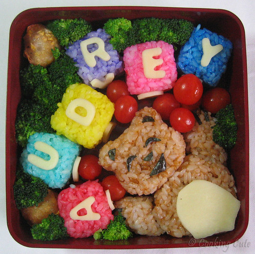 [single bento tier with colored rice blocks, teddy bear, dumplings, and veggies]