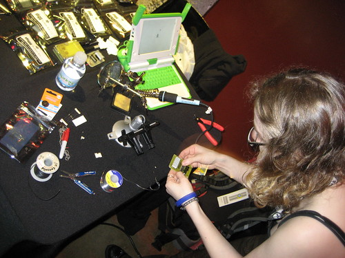 partygoers assemble circuit boards using a soldering pen