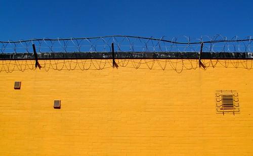 Muro amarillo con alambre de espino en la parte superior