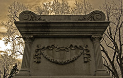 sepia tombstone... (kalurah) Tags: flowers trees shadow sky blackandwhite sun sunlight floral cemetery grave up stone sepia clouds contrast dark shadows gloomy dusk headstone tomb columns rings gloom ribbon dusky apocalyptic oddfellows pedestal nikond40