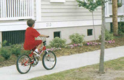 Boy bicycling on sidewalk 02
