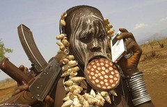 Mursi Tribeswoman with iPod and AK-47 - by neyoung82