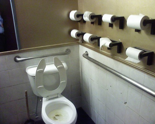 A toilet with 8 toilet rolls on a nearby wall
