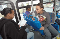 Aboard an Annapolis Transit bus, Chanica Massey (right) talks to Shawana Williams after handing her a brochure