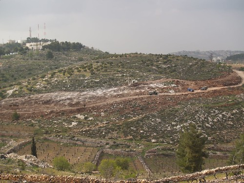 Path of wall, bulldozers destroying land