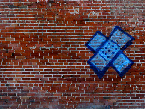 graffiti of blue bandaids, one crossed over the other to make an x, on a brick wall