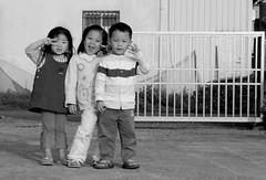 Smiles! (Mie_J) Tags: portrait people bw cute smile kids children taiwan lovely lukang aquafarm 20070412