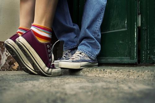 Fotografía de los pies de una parejita besandose, ella con calcetines de colores y el con vaqueros, ambos con Convers All Stars