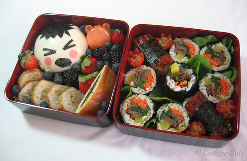 [first bento tier with steamed bun, grilled banana cake, and fruit; second bento tier with kim bap and unagi nigiri sushi]